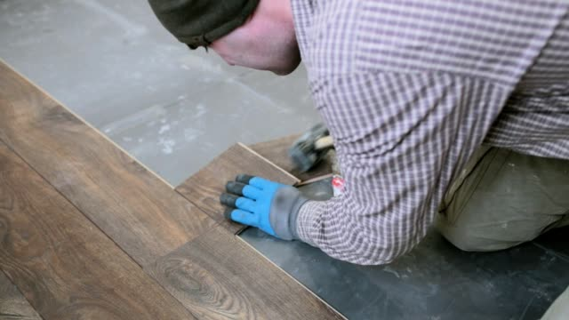 homeowner installs brown laminate flooring. - installing stock videos and b-roll footage