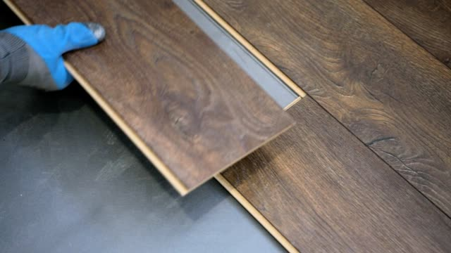 homeowner installs brown laminate flooring. - installing stock videos & royalty-free footage