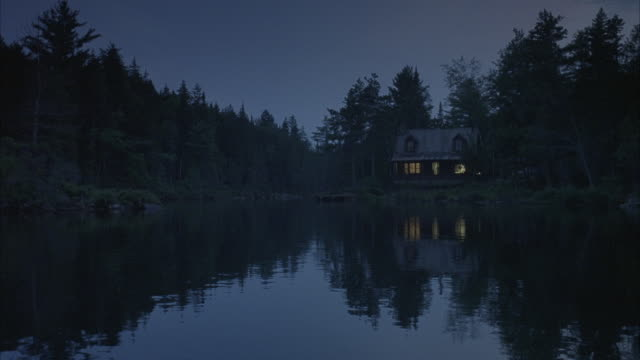 vidéos et rushes de a homeowner searching with a flashlight outside his lakeside cabin. - lampe de poche