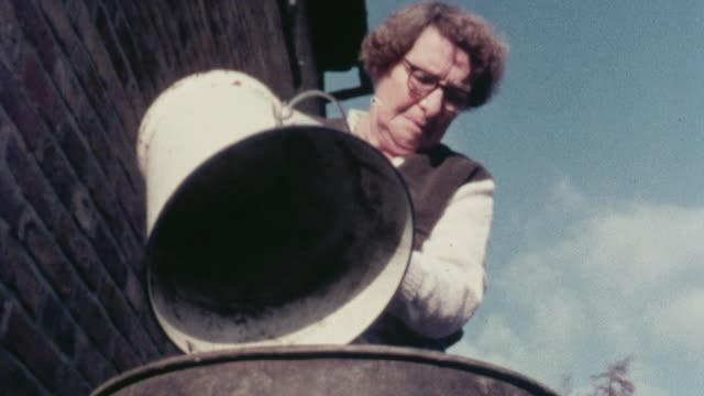 1976 MONTAGE Homeowners dumping household garbage into trash cans / Stevenage, Hertfordshire, United Kingdom