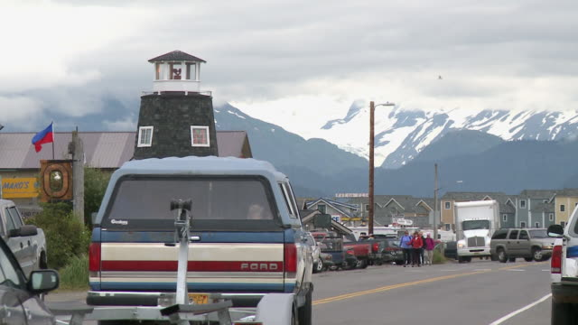 """homer spit road with lighthouse of the salty dawg saloon to left, cars passing both directions, houses visible in background, snow capped mountains of kachemak bay state park and wilderness park visible, home, kenai peninsula, alaska."" - homer alaska stock videos & royalty-free footage"