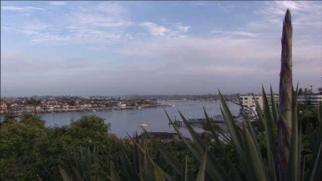 homes and businesses line the shores of the harbor at laguna beach. - カリフォルニア州 ラグナビーチ点の映像素材/bロール