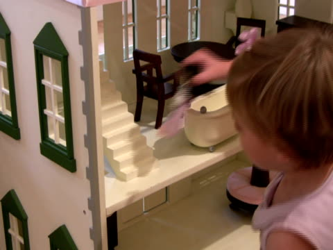 homes and real estate: child plays with doll house - dollhouse stock videos & royalty-free footage