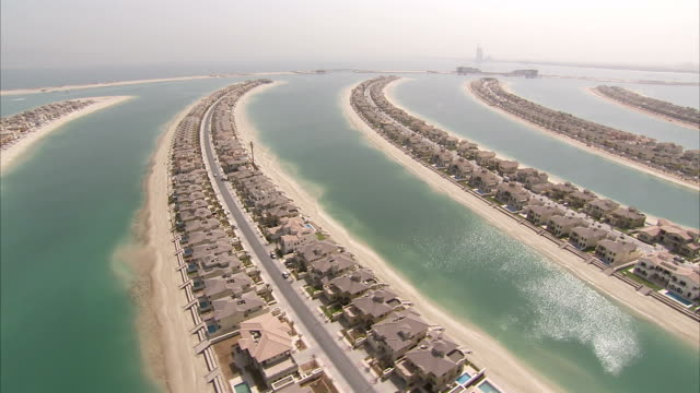 homes cover the man-made fronds of the palm island in the united arab emirates. - insel stock-videos und b-roll-filmmaterial