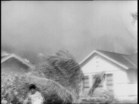 Homes on fire and people running around a residential area of Honolulu / Hawaiian civilians helping wounded / families at shelter at Hawaiian...