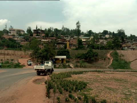 ws pan homes on hill to bridge over highway that was damaged by shrapnel / kigali, rwanda - キガリ点の映像素材/bロール