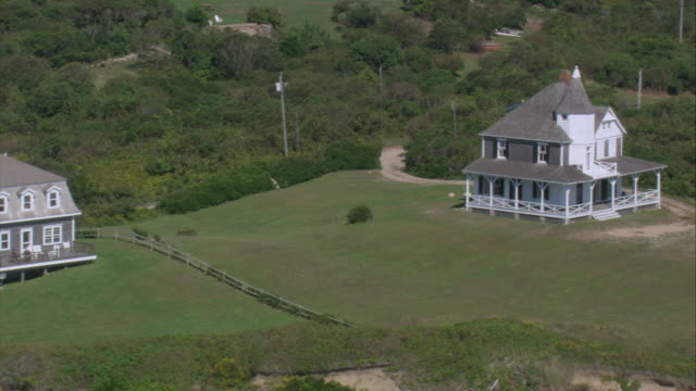 aerial homes on the mohegan bluffs perched above the atlantic ocean / block island, rhode island, united states - 闊銀幕 個影片檔及 b 捲影像