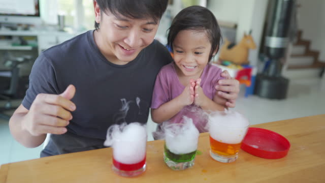 homeschooling, asian man and little boy learning science together at home. - scientific experiment stock videos & royalty-free footage