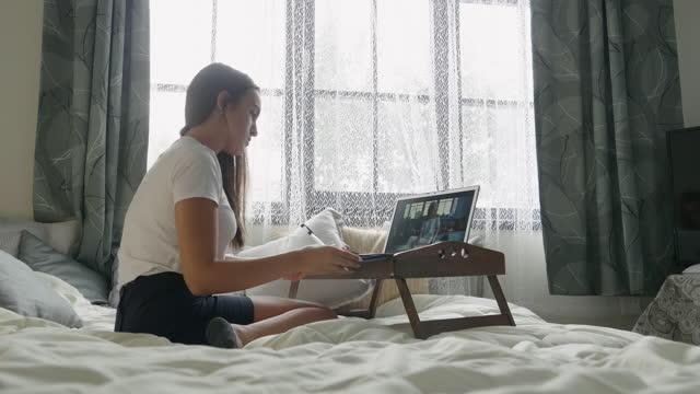 covid-19パンデミック中のホームスクーリング。彼女の寝室で彼女のベッドに座っている間、彼女のラップトップ上のオンラインクラスに出席する集中学生。ティーンエイジャーのeラーニング� - 中等後教育点の映像素材/bロール