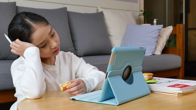 homeschooling - elementary student feeling tired due to watch tablet pc while eating snack - ため息点の映像素材/bロール