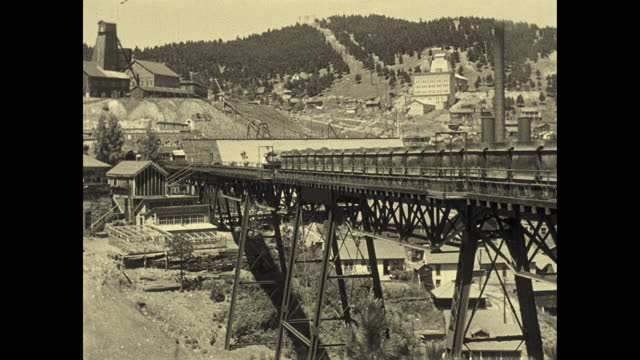 vidéos et rushes de 1924 b/w montage homestake gold mine. large complex of mining buildings, conveyor belts, trestles, trains + smokestacks in valley / lead, south dakota, usa - 1924