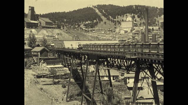 1924 B/W MONTAGE Homestake Gold mine. Large complex of mining buildings, conveyor belts, trestles, trains + smokestacks in valley / Lead, South Dakota, USA
