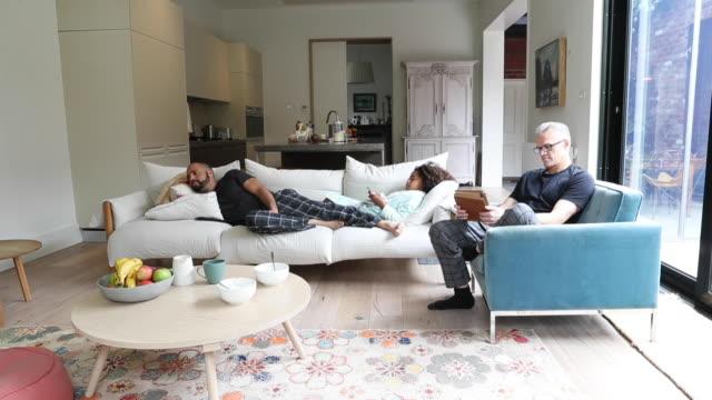 vídeos y material grabado en eventos de stock de homosexual couple and daughter enjoying quiet weekend time at home - bolsa reutilizable