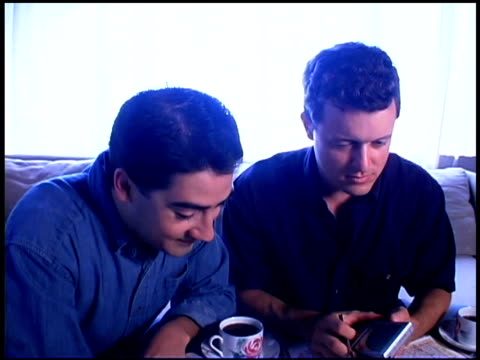 stockvideo's en b-roll-footage met homosexual couple planning vacation with map and pda - elektronische organiser