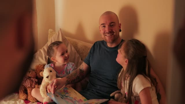 homosexual couple reading their daughters a goodnight story - young family stock videos & royalty-free footage
