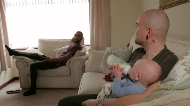 homosexual guy feeding the baby - adoption stock videos & royalty-free footage
