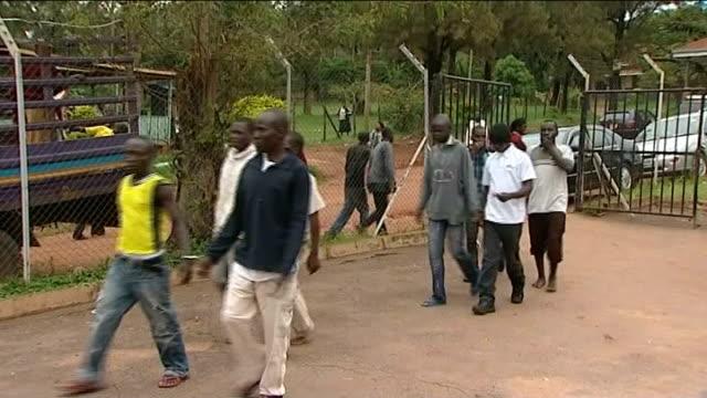 vidéos et rushes de british theatre producer goes on trial over 'gay play'; uganda: kampala: ext handcuffed men along towards court entrance david cecil in corridor of... - kampala