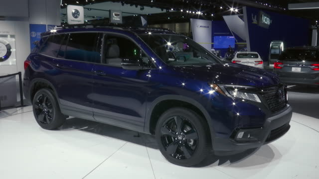 SHOT Honda logo on wall ZOOM OUT WS driver side profile of Honda Passport / ZO WS front quarter passenger side POV / CLOSE UP Passport script on rear...