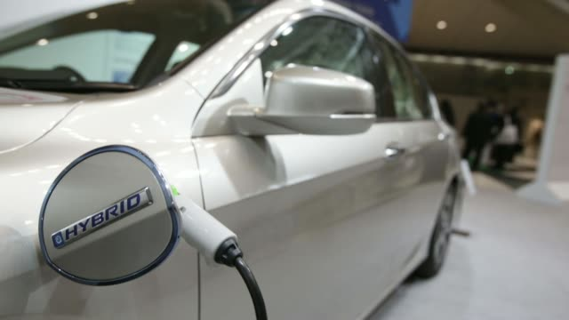 A Honda Motor Co Accord plug in hybrid electric vehicle sits on display at Automotive World 2014 in Tokyo Japan on Wednesday Jan 15 A charging cable...