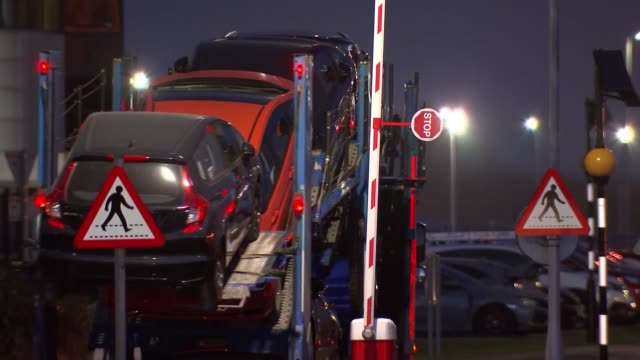 honda to close swindon factory and relocate production to japan; england: wiltshire: swindon: ext / night lorry carrying cars along past barrier - wiltshire stock videos & royalty-free footage