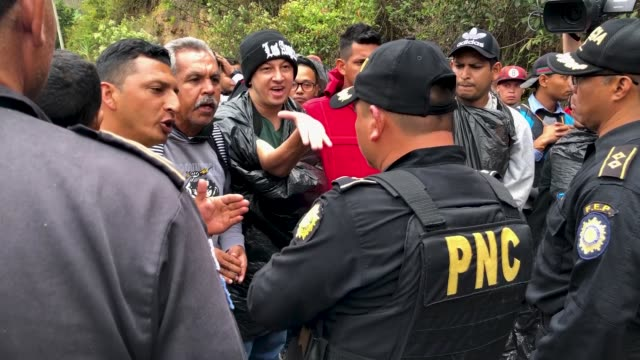 honduran migrants, who are part of a new 'migrant caravan', argue with police blocking a roadway to a border checkpoint into guatemala on january 16,... - agua点の映像素材/bロール
