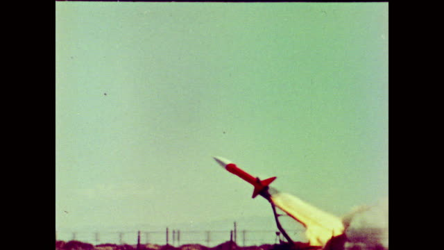 honest john missile shoots into the sky before disappearing inside a purple haze - 冷戦点の映像素材/bロール