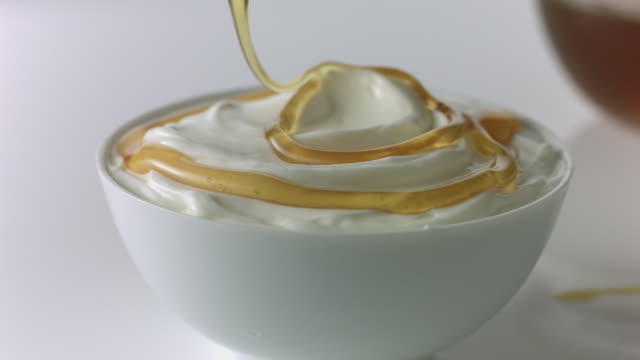 Honey dipper drizzles honey over yogurt