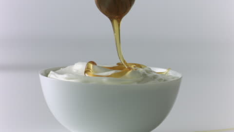 vídeos y material grabado en eventos de stock de honey dipper drizzles honey over yogurt  - miel