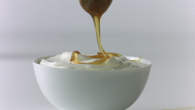 honey dipper drizzles honey over yogurt  - yoghurt stock videos and b-roll footage