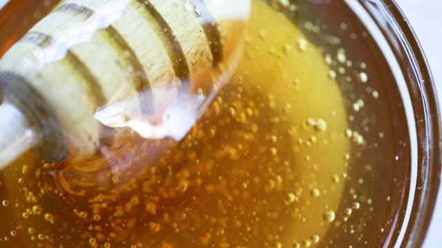 Honey dripping from honey-dipper in glass jar.