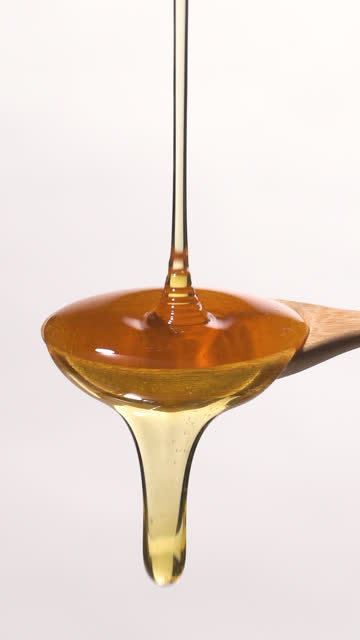 (slow motion and vertical) honey falling from a wooden spoon - syrup stock videos & royalty-free footage