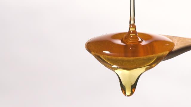 vídeos y material grabado en eventos de stock de (cámara lenta) miel cayendo de una cuchara de madera con espacio de copia - miel