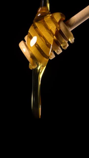 vídeos y material grabado en eventos de stock de (en tiempo real y vertical) miel que fluye de un osa mayor de miel de madera - fondos simples