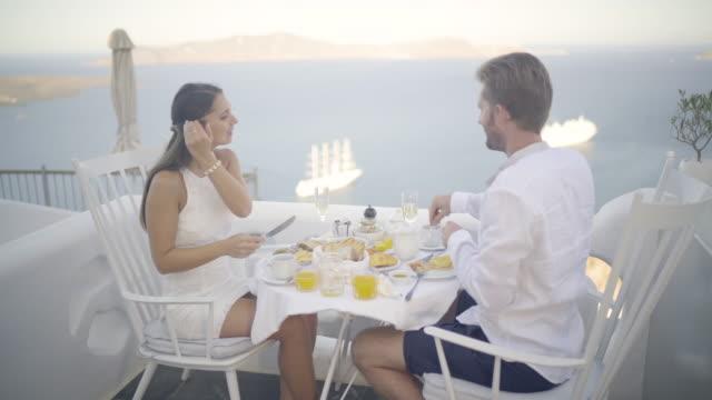 honeymoon couple having breakfast on santorini greece - 対面点の映像素材/bロール