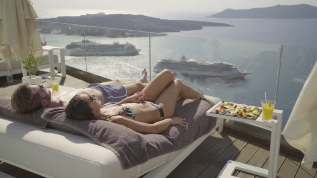 honeymoon couple relaxing at poolside with amazing view - sunbathing stock videos and b-roll footage