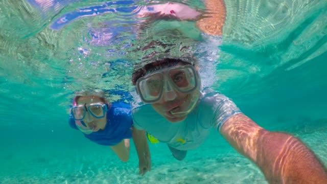 honeymoon couple snorkeling in rarotonga lagoon cook islands. - rarotonga stock videos & royalty-free footage