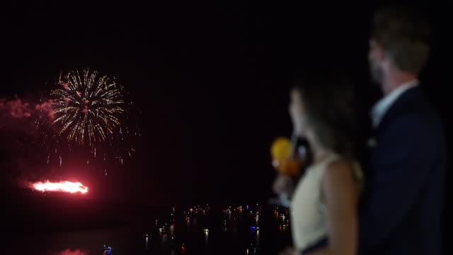 stockvideo's en b-roll-footage met honeymoon couple watching firework - tropische drankjes
