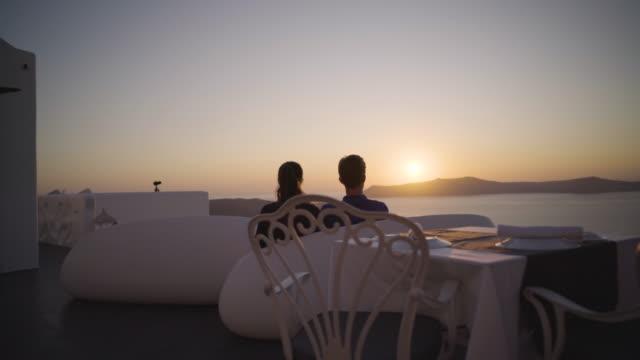 honeymoon couple watching sunset over island - santorini stock videos and b-roll footage