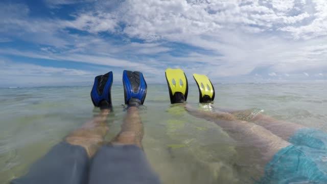 honeymoon couple with snorkeling gear relaxing after snorkel activity in rarotonga cook islands - rarotonga stock videos & royalty-free footage
