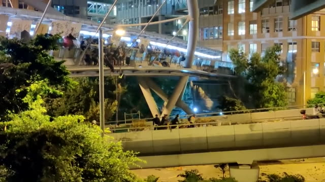 hong kong activists escape siege at the polytechnic university by abseiling from bridge and driven away by mopeds - free falling stock videos & royalty-free footage