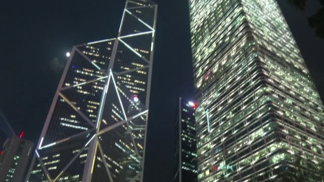 vidéos et rushes de hong kong authorities braced for more protests; hong kong: ext / night moon in the sky low angle view lit up skyscrapers tilt down crowd of... - authority