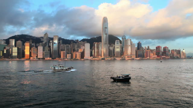 ws hong kong business district with bank of china tower, 2 international finance centre and victoria harbor with boats at sunset / china - bank of china tower hong kong stock videos and b-roll footage