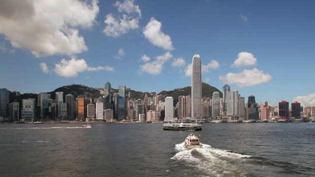 ws hong kong business district with bank of china tower and 2 international finance centre seen across victoria harbor with boats in foreground / china - bank of china tower hong kong stock videos & royalty-free footage