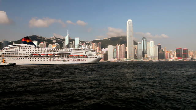 ws hong kong business district with bank of china tower and 2 international finance centre seen across victoria harbor with large cruise ship in foreground / china - bank of china tower hong kong stock videos and b-roll footage