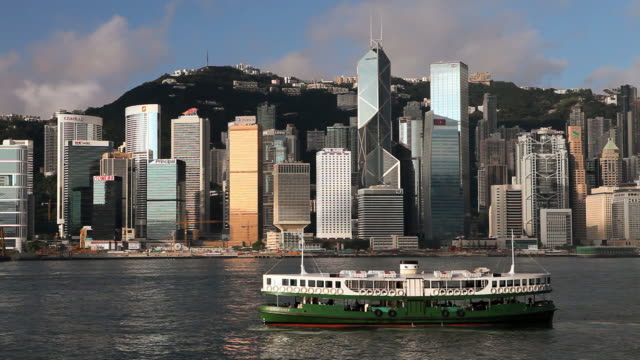 ws hong kong business district with bank of china tower and victoria harbor with ferry boat in foreground/ china - bank of china tower hong kong stock videos and b-roll footage