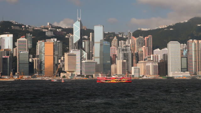 ws hong kong business district with bank of china tower seen across victoria harbor with ferryboats at sunset / china - bank of china tower hong kong stock videos and b-roll footage