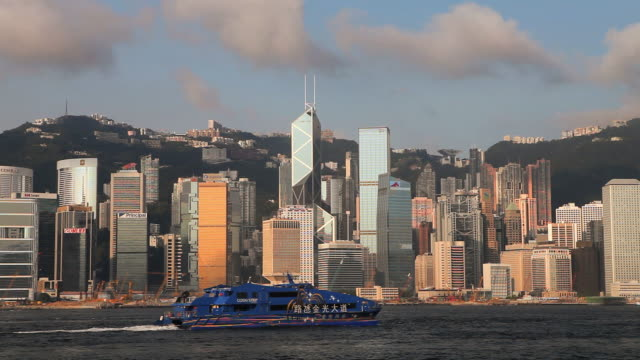 ws hong kong business district with bank of china tower seen across victoria harbor with ferryboat in foreground / china - bank of china tower hong kong stock videos & royalty-free footage