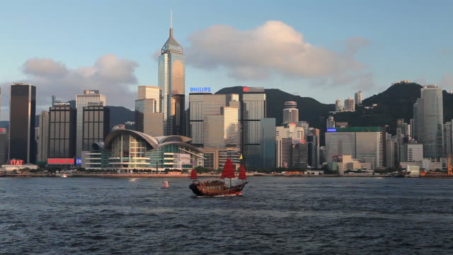 ws hong kong business district with central plaza building seen across victoria harbor with junk boat in foreground / china - central plaza hong kong stock videos & royalty-free footage