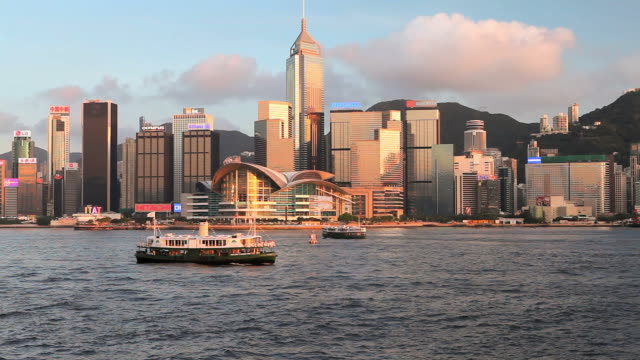 ws hong kong business district with central plaza building seen across victoria harbor with ferry boats in foreground at sunset/ china - central plaza hong kong stock videos & royalty-free footage