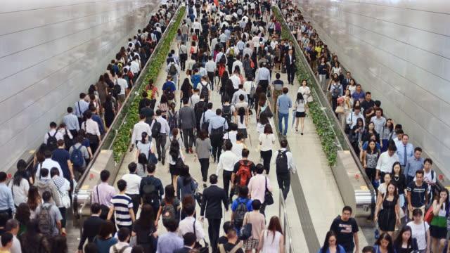 vidéos et rushes de hong kong, business people and commuters using escalators inside an underground train subway station - explosion démographique